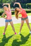 2 друз в шортах практикуя представления йоги Стоковые Изображения