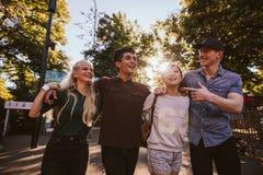 4 друз гуляя в парке атракционов Стоковая Фотография RF