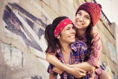 2 друз девочка-подростков брюнет в обмундировании битника (джинсы замыкают накоротко, keds, рубашка шотландки, шляпа) с скейтборд Стоковое Изображение
