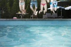4 друз держа руки и скача в бассейн, средний-воздух Стоковые Фотографии RF
