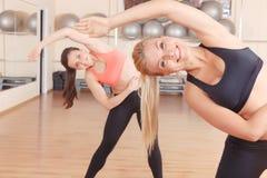 2 друз делая протягивающ тренировки в спортзале Стоковое Фото