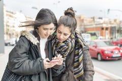 2 друз женщины смотря сообщение на умном телефоне Стоковая Фотография