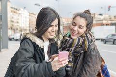 2 друз женщины утехи битника используя умный телефон Стоковые Фото