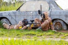 2 друз защищают старый автомобиль в полете пейнтбола Стоковое фото RF