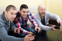 3 друз играя видеоигры Стоковая Фотография