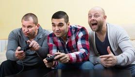 3 друз играя видеоигры Стоковое Изображение