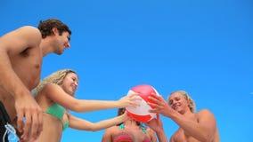 4 друз играя с раздувным шариком пляжа акции видеоматериалы
