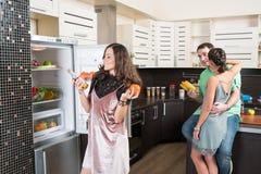 3 друз имея потеху в кухне Стоковое Изображение
