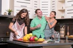 3 друз имея потеху в кухне Стоковое фото RF