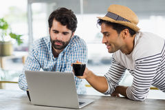 2 друз используя компьтер-книжку пока имеющ чашку кофе Стоковые Фото