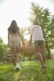 2 друз идя в парк для того чтобы иметь пикник и нося корзину пикника на весенний день, вид сзади Стоковые Фото