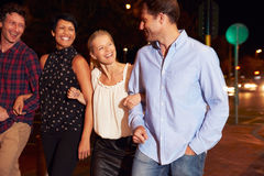 4 друз идя через городок совместно на ночу Стоковые Изображения