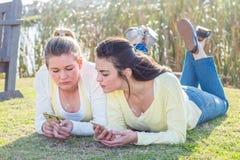 2 друз кладя на траву в парке взаимодействуя Стоковое Изображение RF