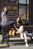2 друз маленькой девочки сидя на стенде в городском центре Стоковое фото RF
