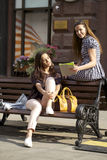 2 друз маленькой девочки сидя на стенде в городском центре Стоковое Фото