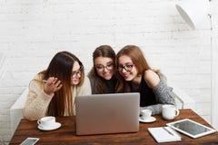 3 друз молодых женщин с компьтер-книжкой Стоковые Фото
