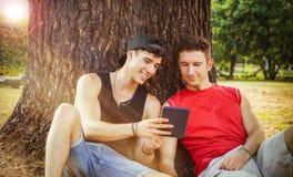 2 друз наблюдая что-то на таблетке или ebook Стоковое фото RF