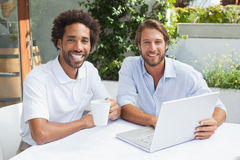 2 друз наслаждаясь кофе вместе с компьтер-книжкой Стоковая Фотография RF
