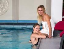 2 друз наслаждаясь днем на бассейне гостиницы Стоковые Изображения