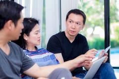 3 друз на линии с множественными приборами и говоря сидеть на софе Стоковые Фото