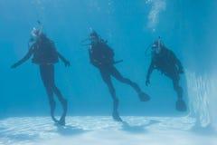 3 друз на тренировке акваланга погруженного в воду в бассейне Стоковые Фотографии RF