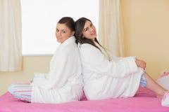 2 друз нося купальные халаты сидя спина к спине Стоковое Фото