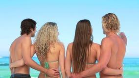4 друз обнимая один другое на пляже акции видеоматериалы