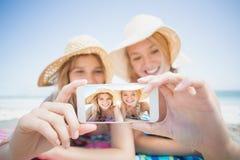 2 друз принимая selfie пока лежащ на пляже Стоковое Изображение RF