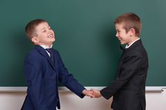 2 друз рукопожатие, мальчик начальной школы около пустой предпосылки доски, одели в классическом черном костюме, зрачке группы, e Стоковое Изображение RF
