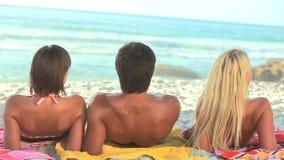 3 друз сидят на их полотенцах на песке сток-видео