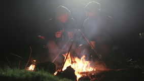 2 друз сидят рядом с костром в древесине на ноче, говоря и выпивая чай акции видеоматериалы
