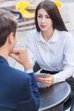2 друз сидя в кафе и обсуждая их дело Стоковые Изображения RF