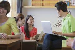 3 друз сидя в кофейне, используя компьтер-книжку и говорить Стоковая Фотография