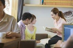 3 друз сидя в кофейне, чтении, обсуждая Стоковое Изображение
