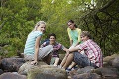 4 друз сидя на камнях Стоковые Фото
