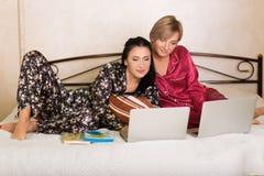 2 друз сидя на компьтер-книжках Стоковое фото RF