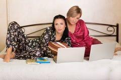 2 друз сидя на компьтер-книжках Стоковые Фото