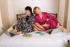 2 друз сидя на компьтер-книжках Стоковая Фотография