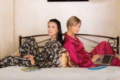 2 друз сидя на компьтер-книжках Стоковое Фото