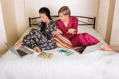 2 друз сидя на компьтер-книжках Стоковые Фотографии RF