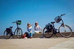 2 друз сидя на пляже с велосипедами Стоковая Фотография