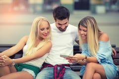 3 друз сидя на стенде и смотря телефон Стоковое Изображение