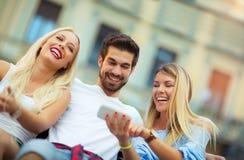 3 друз сидя на стенде и смотря телефон Стоковое фото RF