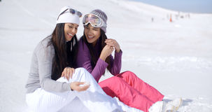 2 друз сидя совместно на солнечном холме лыжи Стоковые Фото