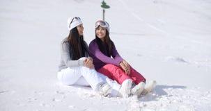 2 друз сидя совместно на солнечном холме лыжи Стоковое Изображение RF