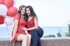 2 друз сидя с воздушными шарами outdoors Стоковое Изображение RF
