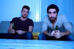 2 друз смотря запальчиво ТВ с пивом и обломоками Стоковые Фото