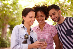 3 друз смотря и усмехаясь на мобильном телефоне Стоковое Изображение RF