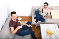 2 друз с пивом и обломоки в живущей комнате Стоковая Фотография RF