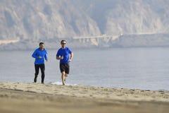 2 друз людей бежать совместно на bachground горы побережья песка пляжа в здоровой концепции образа жизни Стоковое фото RF
